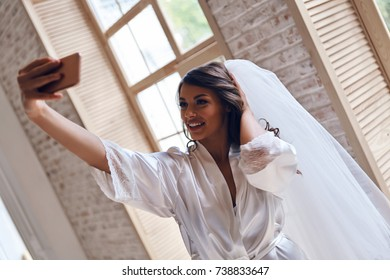 Charming bride. Attractive young woman in silk bathrobe and veil smiling while taking selfie near the window
