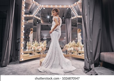 Charming bride.  Full length of attractive young women wearing amazing wedding dress while standing in front of the mirror in bridal shop