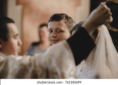 The charming bride and groom standing in the church