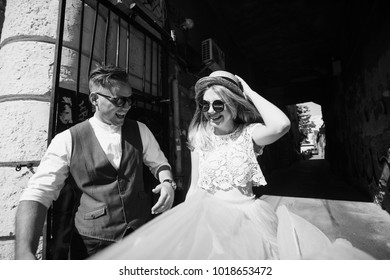 The charming bride and groom walking along street