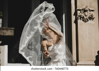 The charming bride stands near building