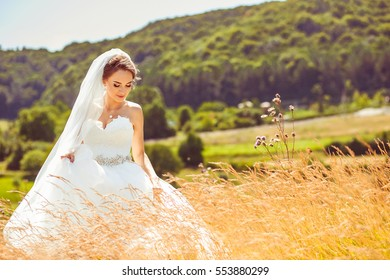 The charming bride stands on the forest