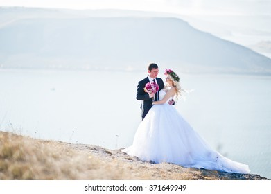 Charming bride in a wreath and elegant groom on landscapes of mountains, water and blue sky at sunny weather