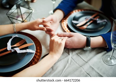 Charming bridegroom holds the bride's hands behind a served table with plates and appliances