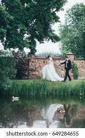 The charming brides and groom walking near lake