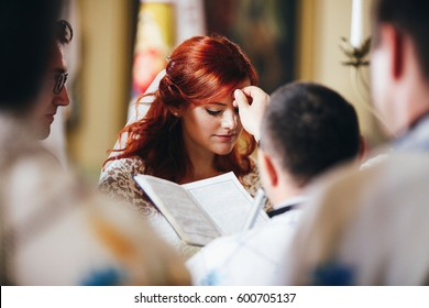 The charming brides stand in the church