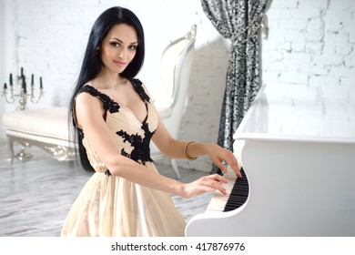 Charming brunette with long hair in evening dress playing the piano.