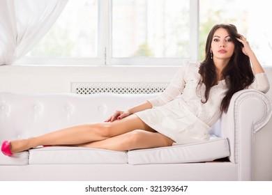 Charming brunette posing on the white sofa