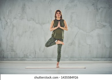 Charming brunette standing on the mat in half lotus pose.