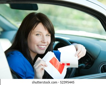 Charming brunette teen girl sitting in her car tearing a L-sign after having her driver's licence