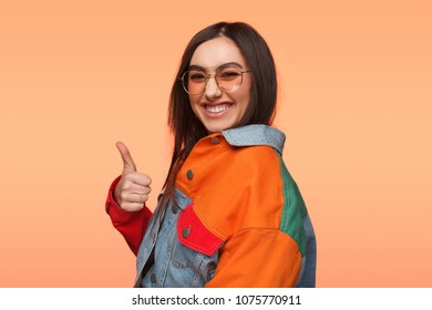 Charming brunette in trendy colorful denim jacket and glasses holding thumb up laughing at camera.
