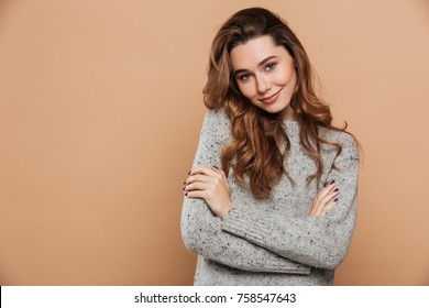 Charming brunette woman with curly hair standing with hands folded, looking at camera, isolated over beige background
