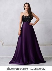 Charming brunette woman dressed in formal maxi dress with top decorated with black sequins and purple satin bottom. Female model posing in elegant evening gown against white wall on background.