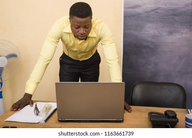 Charming businessman leaning on a conference table in the office and looking on laptop