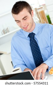 Charming businessman using a laptop in the kitchen at home