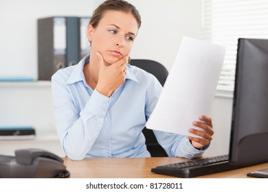 Charming businesswoman concentrating on a paper in her office