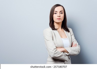 Charming businesswoman. Confident young businesswoman keeping arms crossed and looking at camera while standing against grey background