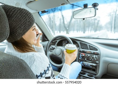 Charming businesswoman drinking cup while driving to work in winter day