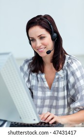 Charming businesswoman with headset on working at a computer in a call-center