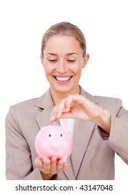 Charming businesswoman saving money in a piggybank isolated on a white background