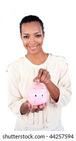 Charming businesswoman saving money in a piggybank against a white background
