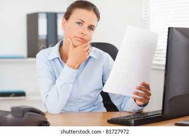 Charming businesswoman thinking of a paper in her office