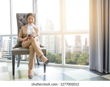 Charming businesswoman using digital tablet to checking on work progress in modern office. asian confident CEO women in her work place