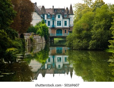 A charming castle on a small river in France.  The castle is built across the river and casts a reflection in the water.  Lots of greenery on both sides of the river.