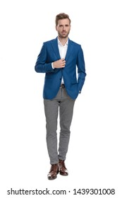 Charming casual guy adjusting his jacket and holding his hand in his pocket while wearing a suit and posing on white studio background