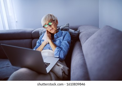 Charming caucasian blond senior woman with eyeglasses sitting on sofa in living room, holding laptop in lap and watching sad movie. Sunday afternoon at home.