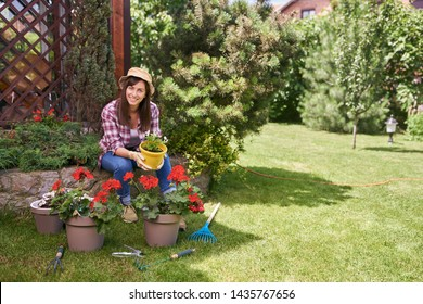 Charming Caucasian brunette dressed in working clothes holding yellow pot with begonia and sitting near other pots with flowers. All aroung gardening tool.