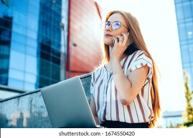Charming caucasian businesswoman with red hair and freckles is using her laptop while having a phone discussion
