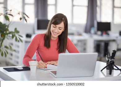 Charming Caucasian businesswoman sitting in moderna office and taking notes in notebook. In front of her laptop.