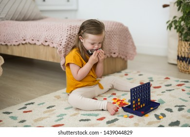 Charming Caucasian girl blonde 4 years old with Down syndrome plays with educational game in the nursery on the floor, close-up, bright interior in the Scandinavian style with mugs