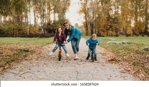 Charming caucasian mother with two kids who are riding joyfully the bike in the park during a walk