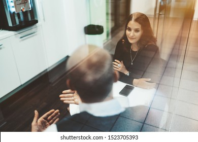 A charming caucasian woman entrepreneur with a long hair is listening attentively her male colleague during a break while both sitting at the table of a modern office kitchen and talking