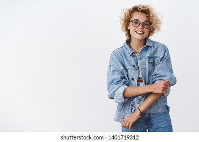Charming charismatic outgoing blond girl with short stylish haircut rolling sleeved on denim jacket and smiling broadly getting ready for productive lucky day standing over white background delighted
