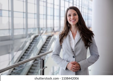 Charming, cheerful, enthusiastic, friendly business corporate executive head shot in large building hall