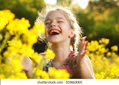 Charming cheerful girl among yellow wildflowers