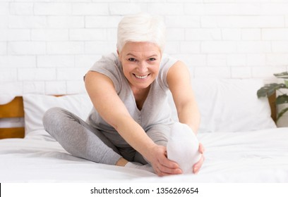 Charming cheerful mature woman stretching her legs and doing yoga in her bed. Waking up and morning routine concept