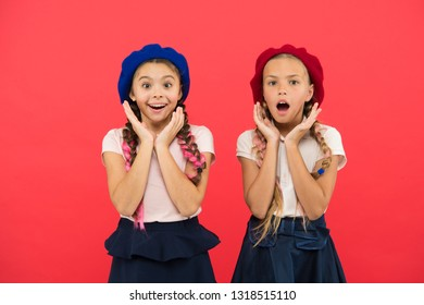 Charming and chic. Cute girls having the same hairstyle. Small children with long hair plaits. Fashion girls with tied hair into braids. Little kids wearing stylish french berets. French style girls.