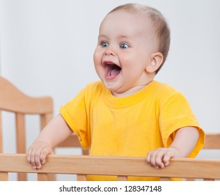 Charming child in the crib. Charming baby in yellow holds the handrails and laughs