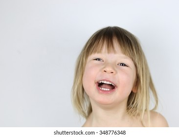 charming child with light hair and dark eyes happily laughs