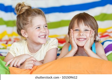 The charming children playing on the bed at home