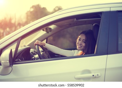 Charming Chinese girl driving a car, smiling toward the destination