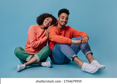 Charming couple in love sitting on blue background and hugging. Joyful woman in orange sweater and man in jeans widely smile on isolated