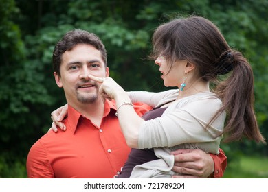 Charming couple of a man and woman. Man holding woman in his hands