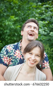 Charming couple of a man and woman standing in the park, man stands behind woman and embraces her