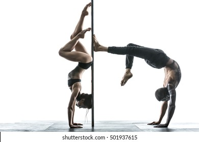 Charming couple of pole dancers with horrific body-art stands on their hands upside down next to a pylon in the studio on the white background. They are using the pylon like a fulcrum. Horizontal.