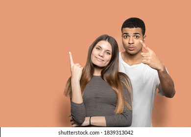 A charming couple is posing on a brown background, wearing t-shirts, pointing up with their hands and smiling at the camera